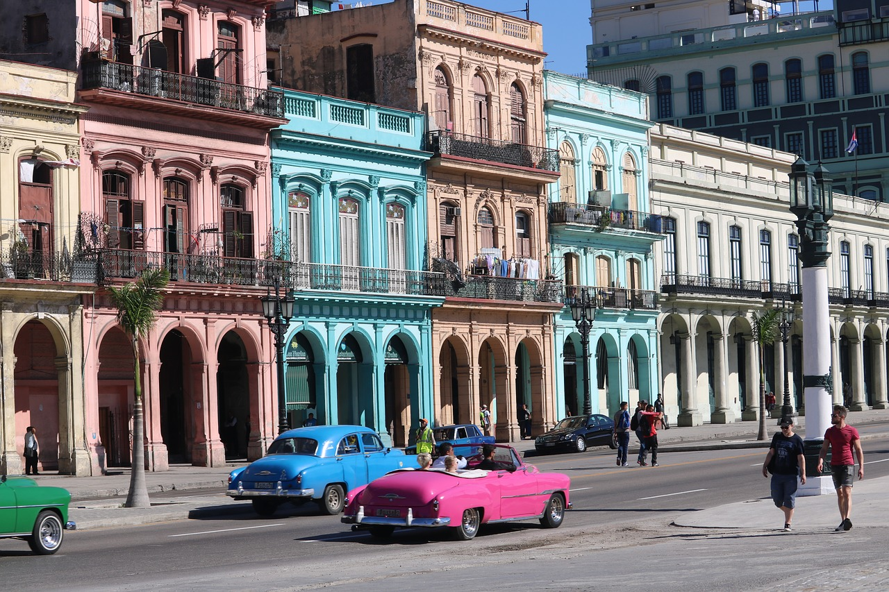 Colourful building facades complementing vintage cars in Cuba.