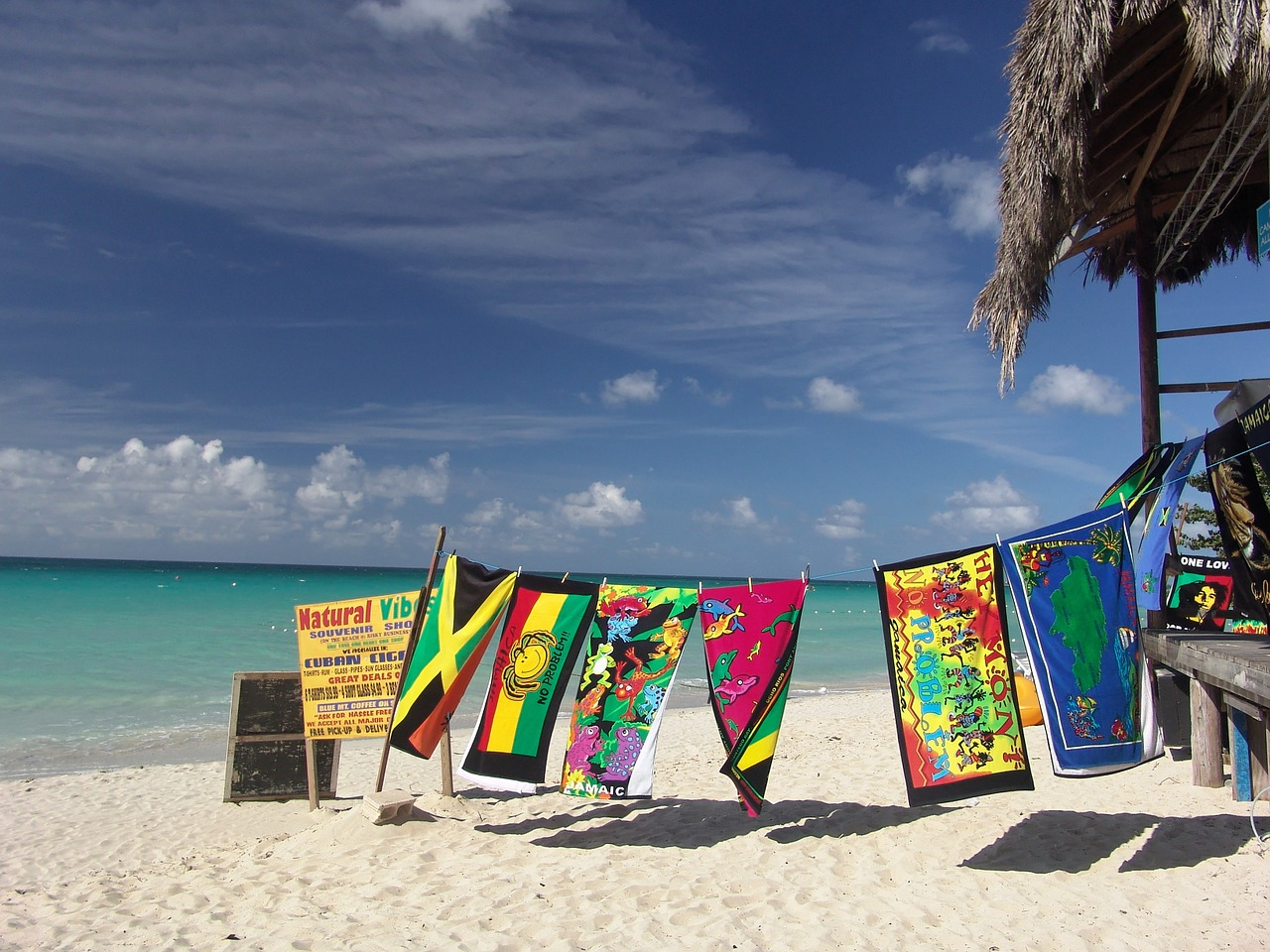 Colourful beach towels hanging to dry on a Jamaican beach.
