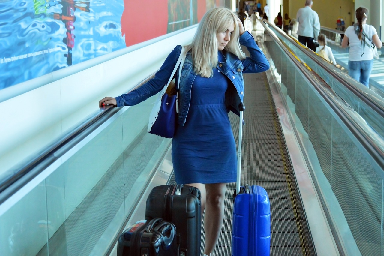 Young woman with luggage at airport who is late for her flight